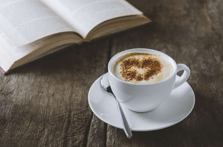 White cup of coffee latte with cinnamon on wooden table with open book with vintage and viggnete tone