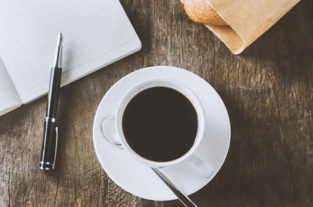 White cup of black coffee with white notebook and pen on wooden table with vintage and vignette tone 写真素材