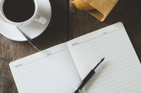 Blank white notebook and pen with cup of coffee on wooden table with vintage and vignette tone