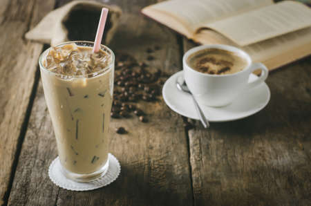 Close up of Iced Coffee on wooden table with cup of lattee and coffee beans 写真素材