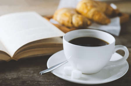 Close up of black coffee with book and croissant on wooden table with vintage and vignette tone