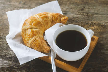 Close up of black coffee with croissant on wooden table with vintage and vignette tone 写真素材