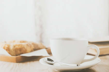 Close up of white coffee cup with croissant on wooden table with vintage and vignette tone 写真素材