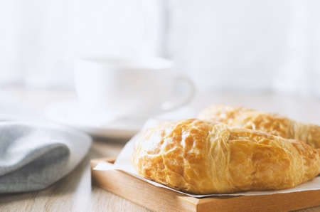 Close up of croissant with cup of coffee on wooden table with vintage and vignette tone