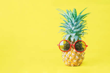 Pineapple with red sunglasses on yellow background - Summer background 写真素材
