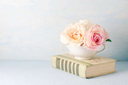 Artificial pink rose flowers in white cup with old book on blue background with vintage tone