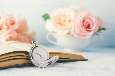 Close up of antique silver pocket watch and opened book with rose flowers on white and blue background with vintage tone
