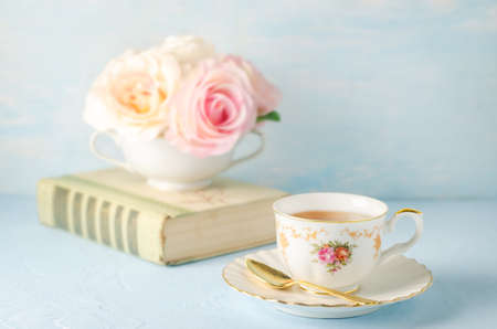 Close up of cup of tea with flowers and book on blue background with vintage tone - Afternoon tea party concept 写真素材 - 131759589