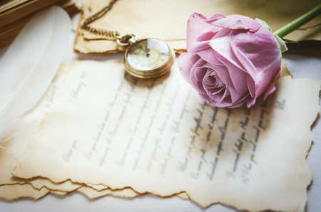 Close up of violet purple rose flower with antique pocket watch and love letters with vintage and vignette tone
