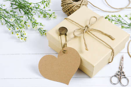 Brown gift box with heart tag label on wooden table with white daisy flower and vintage pin 写真素材 - 145955971