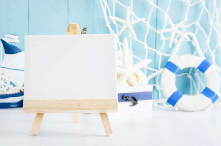 Close up of canvas and wooden easel with sail boat Toy model, ship wheel, rope and seashell on white and blue wooden