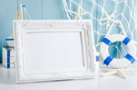 Close up of vintage picture frame with sail boat Toy model, rope and seashell on white and blue wooden background - Nautical background 写真素材