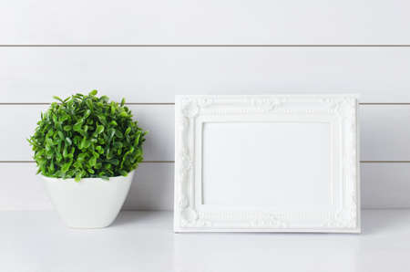 Blank vintage photo frame with green home plant at white vase on white wooden background 写真素材 - 144930457