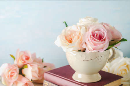 Artificial pink rose flowers in vintage cup with books on blue background with vintage tone