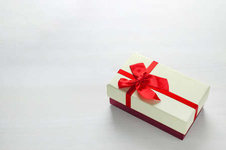 Close up of two tone gift box with red ribbon bow on white wooden background