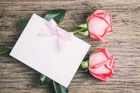 Blank white greeting paper card with pink roses and ribbon on old wooden table 写真素材 - 145955975
