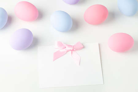 Blank white greeting card with pink ribbon bow and pastel easter eggs on white table 写真素材 - 145955656