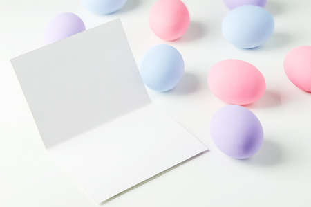 Blank white greeting card with pastel easter eggs on white table background, Easter background 写真素材