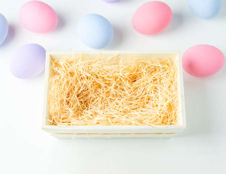 Blank wooden basket with wood wool on white table background with pastel ester eggs