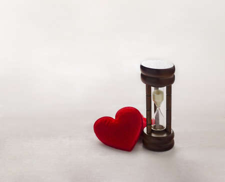 Antique wooden hourglass with red hearts on white wooden table, Time concept