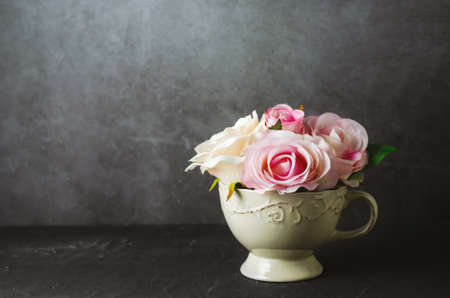 Artificial pink rose flowers in vintage cup on grunge background with vintage tone