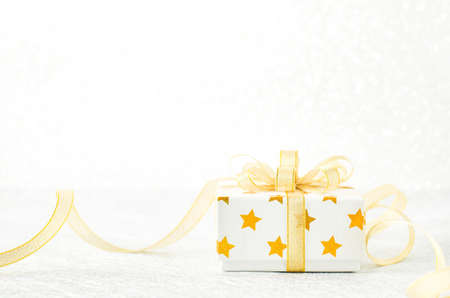 Close up of white gif box with golden star pattern and gold ribbon bow on bokeh background - Christmas background