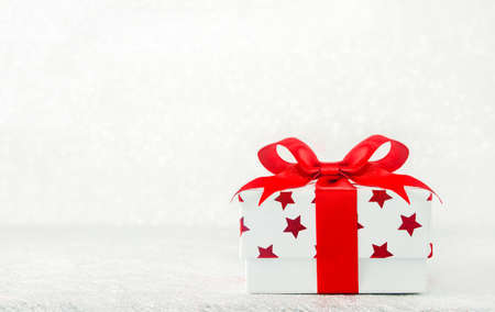 Close up of white gif box with red star pattern and red ribbon bow on bokeh background - Christmas background