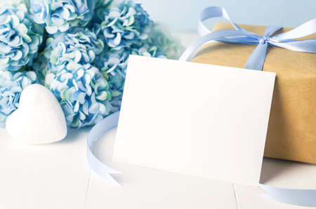 Close up of empty white greeting card  with brown recycle gift box and blue Hydrangea flowers on blue wooden background with soft vintage tone 写真素材 - 144932566