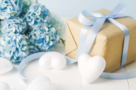 Close up of brown recycle gift box with white heart and blue Hydrangea flowers on blue wooden background with soft vintage tone