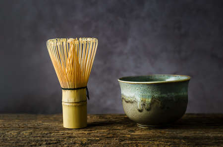 Japanese matcha green tea at homemade clay bowl with bamboo whisk on wooden table with vignette tone 写真素材