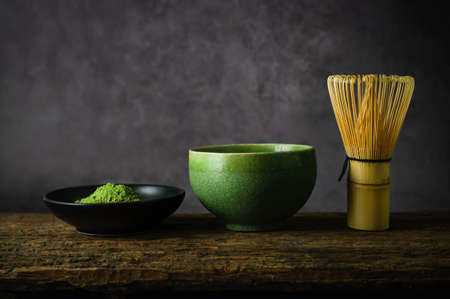 Japanese matcha green tea and matcha green tea powder at homemade clay bowl with bamboo whisk on wooden table with vignette tone 写真素材 - 144932591