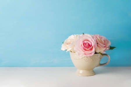 Artificial pink rose flowers in vintage cup on white and blue background with vintage tone