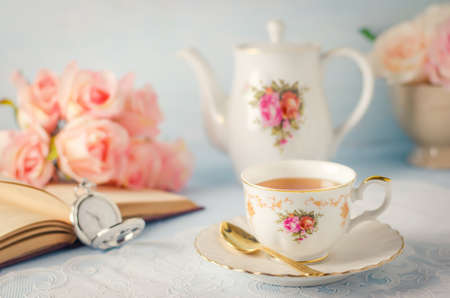 Close up of cup of tea with teapot, rose flowers, pocket watch and book on white