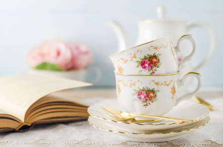 Close up of cup of tea with book, teapot and rose flowers on blue