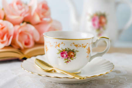 Close up of cup of tea with book, teapot and rose flowers on blue 写真素材 - 145955666