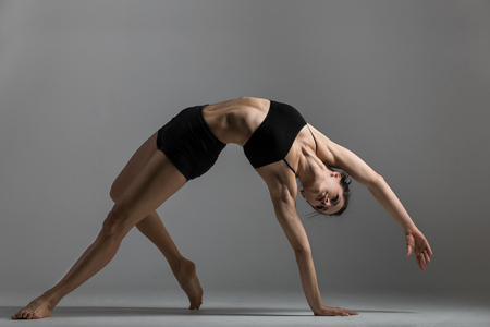 Gymnast girl is training performing exercise bridge