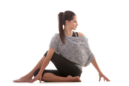 ardha: Sporty Yoga girl on white background performing Ardha Matsyendrasana (Half Lord of the Fishes Pose, Half Spinal Twist Pose or Vakrasana)