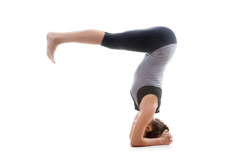 Sporty yoga girl on white background doing a handstand in pose shirshasana (Sirshasana) with bent legs photo