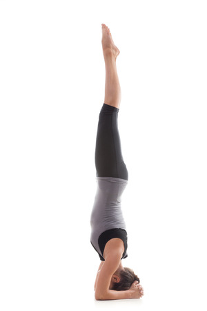 Sporty yoga girl on white background doing a handstand in pose shirshasana (Sirshasana) with straight legs photo