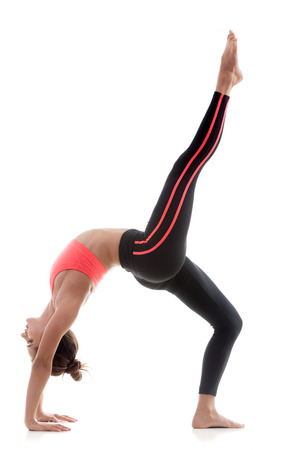 Sporty yoga girl on white background stretching in bridge exercise with one leg stretched out photo