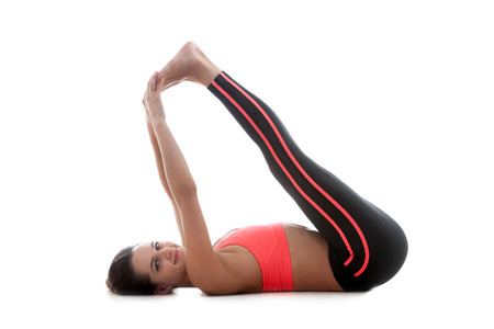 lies down: Sporty yoga girl lies down on white background and holds up both feet while stretching Stock Photo