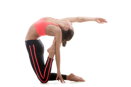 ushtrasana: Sporty yoga girl stands on her knees on white background while stretching in pose ushtrasana (Ustrasana or Camel Pose) Stock Photo