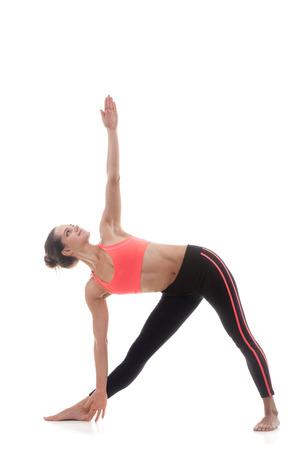 trikonasana: Sporty yoga girl on white background in utthita trikonasana (extended triangle pose)
