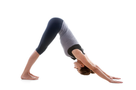 Sporty yoga girl on white background stretching in pose urdhva mukha shvanasana (Upward Facing Dog Pose) Stock Photo