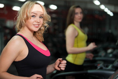 scamper: Smiling sporty girl exercising on cardio trainer, running on racetrack at gym