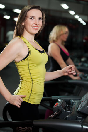scamper: Smiling sporty girl exercising on cardio trainer, treadmill in gym