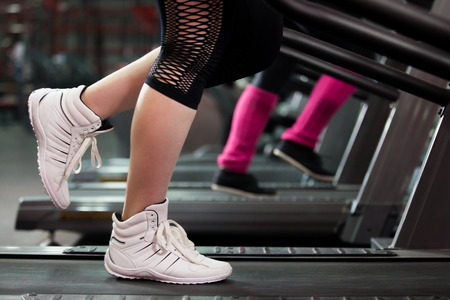 Close-up of women legs in sneakers on treadmill in gym photo