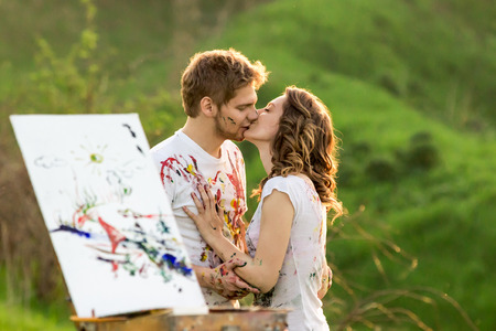 Couple covered in paint kisses behind the sketchbook photo