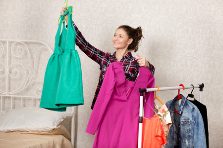 Smiling girl holds two dresses while choosing closes