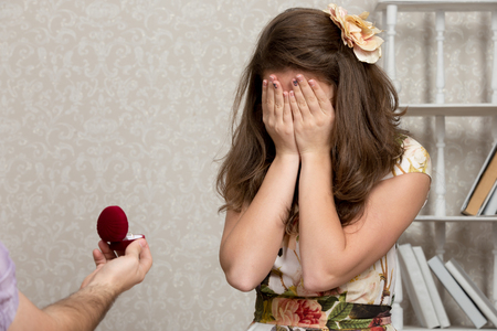 proposed: Girl covers her face with hands after being proposed to